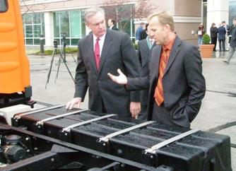 Missouri  Governor Jay Nixon ( L) and  SEV CEO Bryan Hansel examine  truck battery
