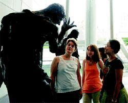 Barbara O?Brien views a sculpture with Simmons students.