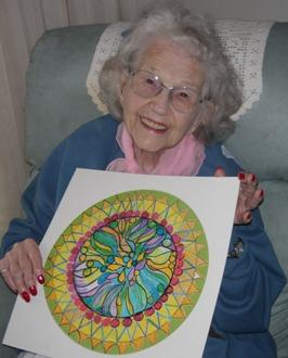 Phyllis Farnell holding her drawing of a mandala.