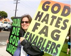 A member of the Westboro Baptist Church smiles as she displays the group's message.