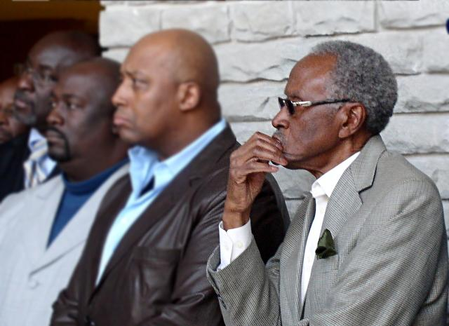"Former mayoral candidate Alvin Brooks listens as the Reverend Wallace Hartzfield says the firing of the city manager was Handled in a ""wrong and immoral\"" way."