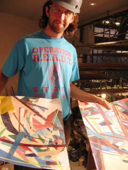 Project manager Daniel Reneau holds up the KCAI student designs for the mural at the Kauffman Center for the Performing Arts.
