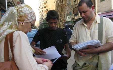 From The Web To The Streets: Ahmed Nasser (right) and Shahinaz Abdel-Wahab hand out petitions for better governance in the Mahdi neighborhood in Cairo. They are part of the April 6th movement, political activists who started as an Egyptian Facebook group.
