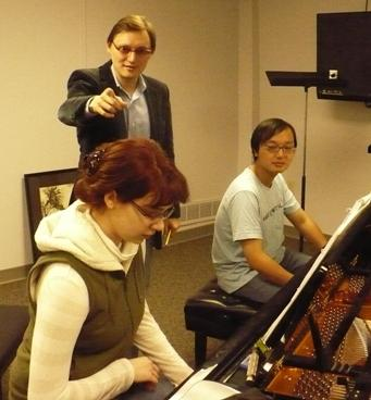 Stanislav Ioudenitch works with students Erin Hale (left) and Yuntian Liu (right).  Photo by Alex Smith / KCUR.