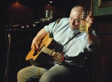 Eddie Delahunt raises his glass as he prepares to sing Irish folk music.