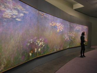 Nicole Myers, associate curator of European Painting and Sculpture, stands in front of the three panels of Claude Monet's <I>Water Lilies</I> triptych. photo: Laura Spencer/KCUR