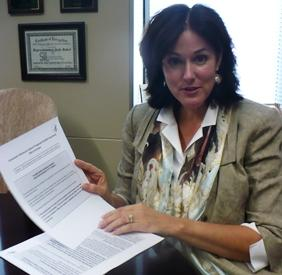 HHS Region 7 Director Judy Baker holds new insurance rate forms that companies in Missouri will now have to submit.