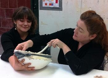 "KCAI student Cydney Ross helping Teri Frame prepare for ""Lavatar's Animals."""