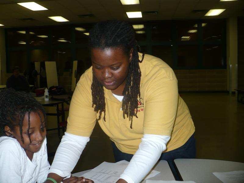 Jamekia Kendrix and her daughter set up for a forum about the future of Kansas City Public Schools