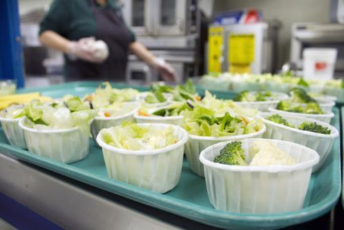 Food service workers set out Individual salads at a school cafeteria in Lincoln, Neb.