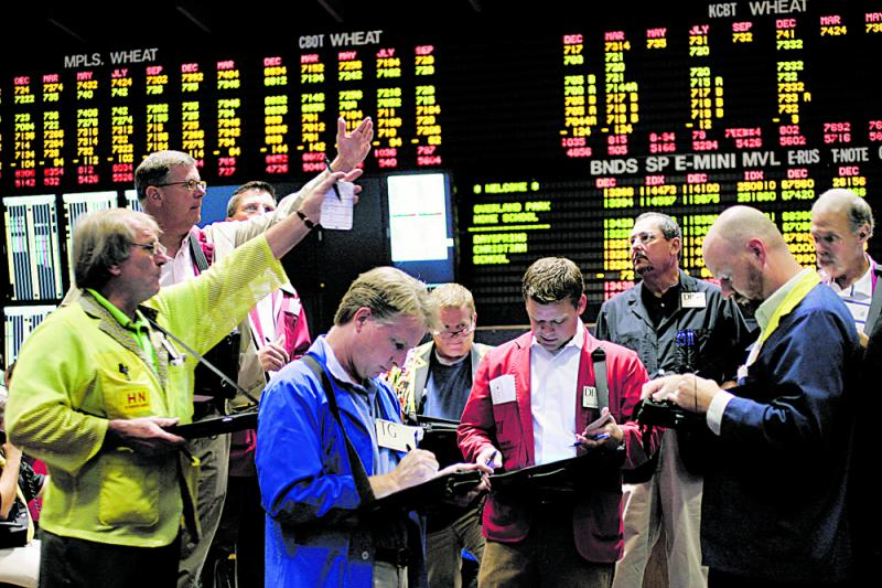 Traders in the wheat futures trading pit at the Kansas City Board of Trade signal each other in September 2010. The KCBOT and Chicago Mercantile Exchange host two of the country's largest commodities markets.