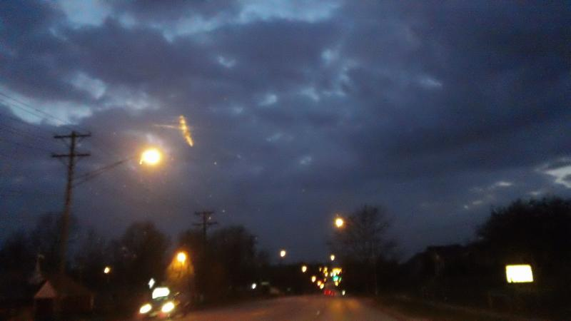 A photo of a sighting over Independence, Mo. in March. The streak of yellow just above the streetlight is still unexplained.