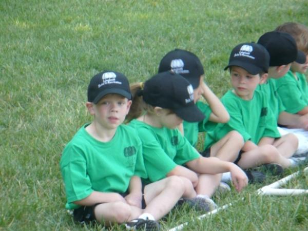 5- and 6-year-old t-ball players sit in line as they wait to have their team pictures taken.