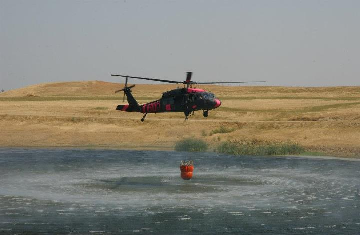 "A Black Hawk helicopter uses the so-called ""Bambi"" bucket to pick up water..."