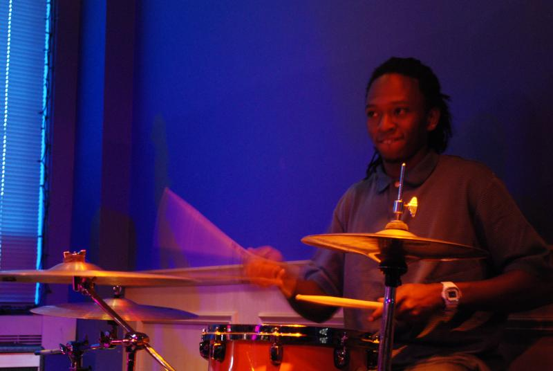 The house drummer, Tyree Johnson, performs during the set between the featured poets and the open mic.