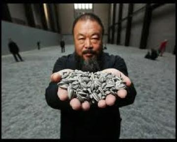 Ai Weiwei with a handful of porcelain sunflower seeds at London's Tate Modern
