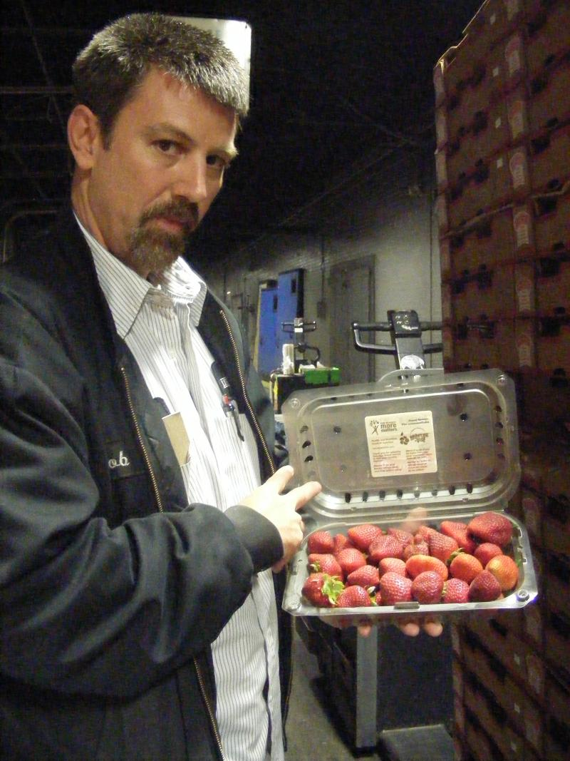 Robbie Mitchell, the night warehouse manager, checks out a load of strawberries from California.