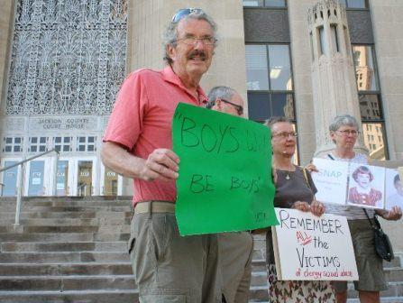Protesters gathered at the Jackson County Court House on Thursday. David Biersmith holds a quote attributed to Bishop Robert Finn who faced trial.