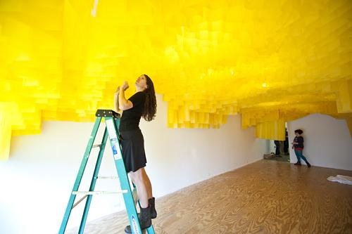 Carrie Scanga makes a final sweep of a golden canopy inspired by bee colonies.  Scanga is working with four area artists to create an experimental, collaborative workspace.