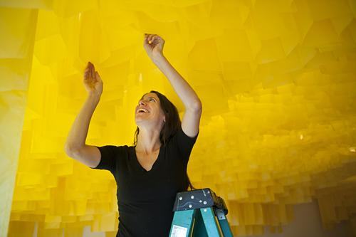 Carrie Scanga adjusts a paper panel in PLUG Projects' gallery space.
