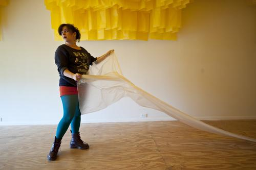 Amy Kligman, a co-curator and artist, drapes the floor with a drop cloth to protect delicate paper panels.