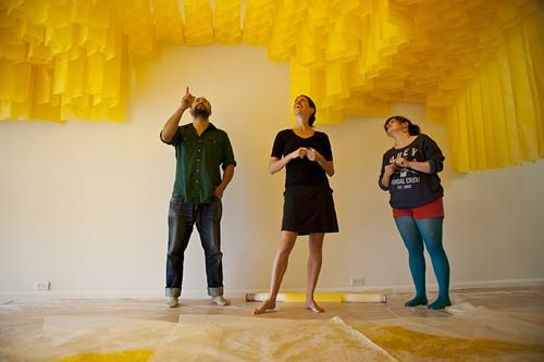 Ron Harrity, (from left) Carrie Scanga, and Amy Kligman peer up to get a better look at the way gallery lights flow the tissue paper honeycomb. Harrity traveled with Scanga from Portland, Maine, to help her install her work.