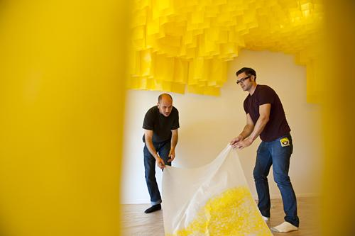 Misha Kligman (from left) and Caleb Taylor, co-curators and artists at PLUG Projects gently move the fragile panels before installing them on the gallery walls.