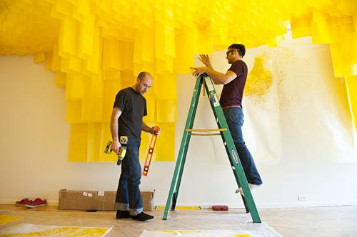 Misha Kligman (from left) and Caleb Taylor, co-curators and artists at PLUG Projects measure and install the painted panels.