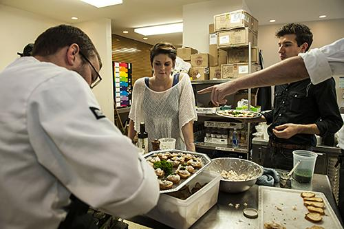 Line cook Logan Taylor spreads homemade Shatto ricotta on crostini as servers Erin Weaver and Alex Walter await the completion of another appetizer tray.