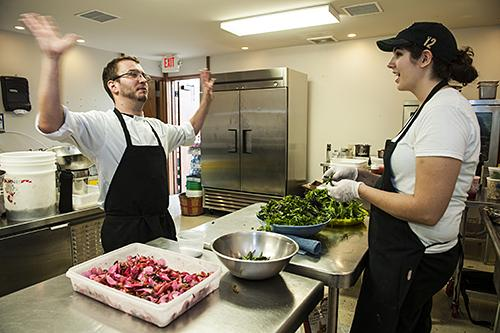 During a pause in the action, line cooks Logan Taylor, from left, and Kristina Trankino joke around in the kitchen as they prepare for the salad course.