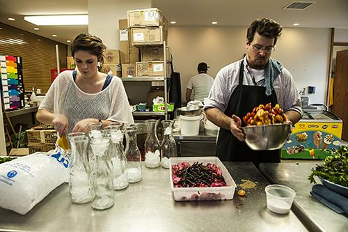 Server Erin Weaver fills carafes full of ice as sous chef Paul Hasty dresses fresh tomatoes.