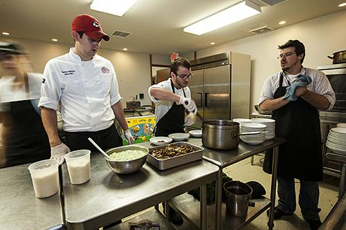 Line cooks Spencer Wohlford and Logan Taylor listen to instructions on plating the gnocchi from sous chef Paul Hasty.