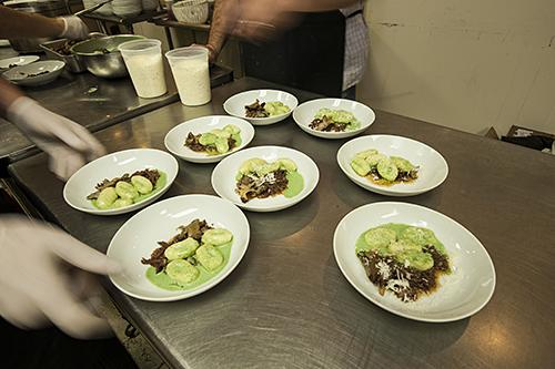 The kitchen team prepares to send out the sheep's milk gnocchi with smoked oxtail.