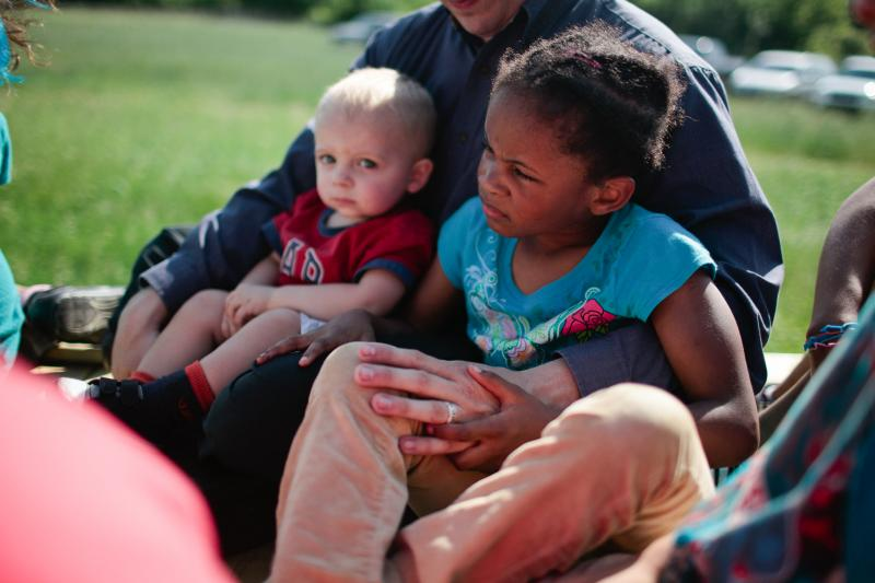 A father holding his biological and foster children. The Adopt KC program works with local churches to see how it can support congregants interested in housing foster kids.