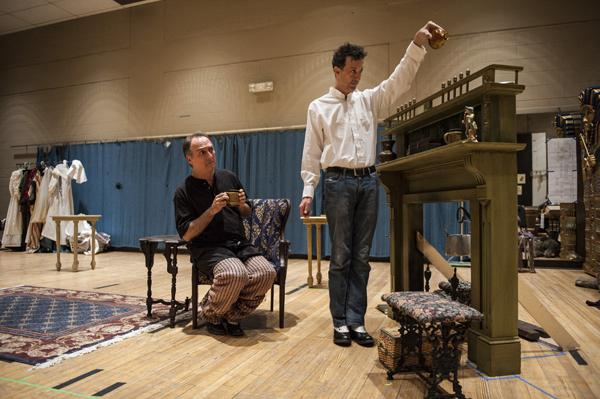 In rehearsal, Mark Robbins, as Lady Enid Hillcrest,  gives a disapproving look as Ron Megee, playing Jane Twisden, pours herself another hot toddy.