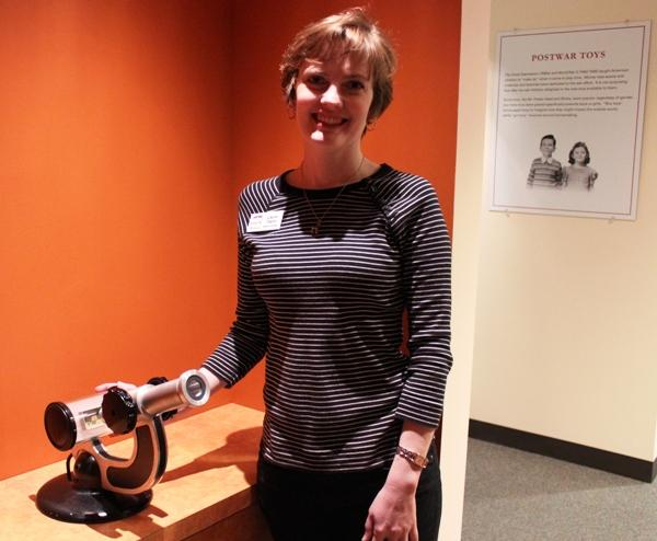 Museum educator Laura Taylor stands next to one of the smallest works in the collection, a micro-curiosity.