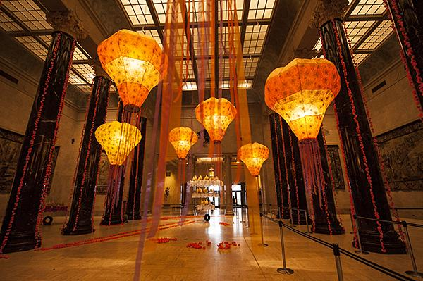 Glowing lanterns in Kirkwood Hall hang from the skylight trailing ribbons at the Nelson-Atkins Museum of Art.