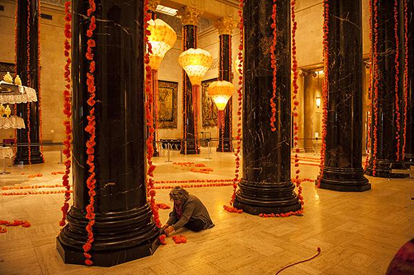 Barbara Clark, of the design department at the Nelson, adheres tissue paper marigolds to the bottom of a column.