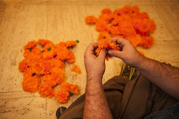 Jake Ludemann, of the design department at the Nelson, fluffs a pile of tissue paper marigolds.