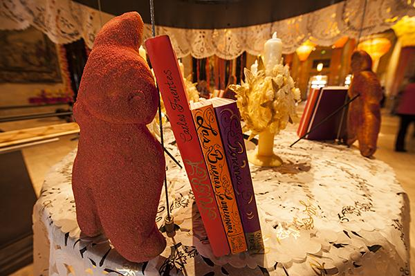 Stylized books, sugared bread, and elaborate candles decorate an altar memorializing Carlos Fuentes.