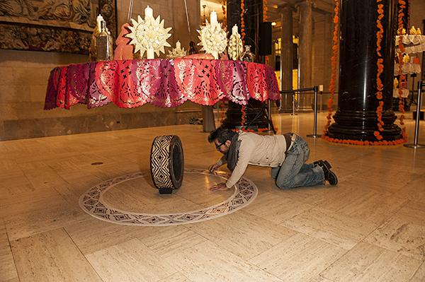 Under close direction from Romero, Israel Garcia, from the Mattie Rhodes Center, adjusts a laminated decoration on the floor.