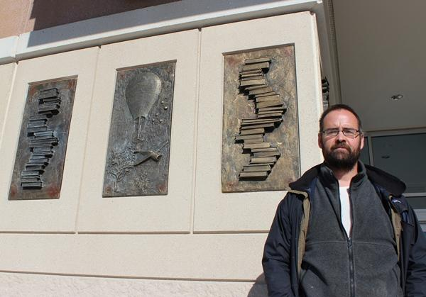 Michael Wickerson, associate professor and chair of sculpture at KCAI, stands in front of three bronze panels.