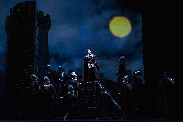 Under a full moon, Kirk Eichelberger, as Ferrando, tells the story of a Gypsy woman burned at the stake many years ago.
