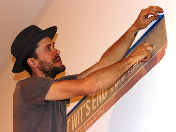 Artist Beniah Leuschke installs the title in Epsten Gallery.