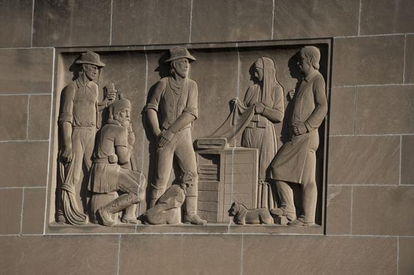 A stone relief of pioneers.