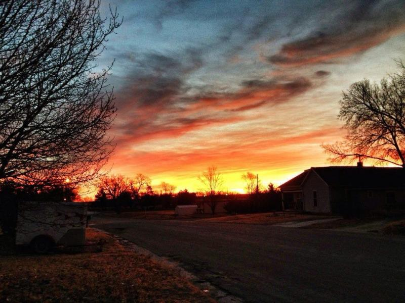 Each day the page starts with a photo of a Kansas sunrise.