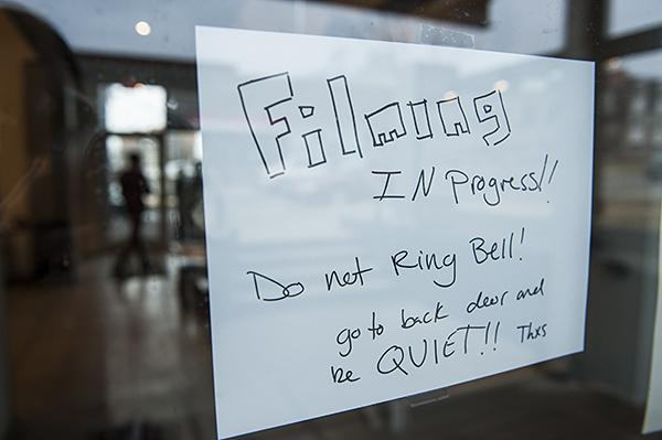 As the Xijing Men work a sign requesting silence is posted on the door of the H&R Block Artspace at the Kansas City Art Institute.