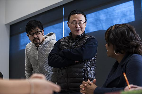 Xijing Men artists (from left) Tsuyoshi Ozawa, of Japan, and Gimhongsok of Korea, discuss the visual languages they are creating during a language exercise.