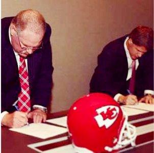 Andy Reed signs his contract as Kansas City Chiefs head coach.