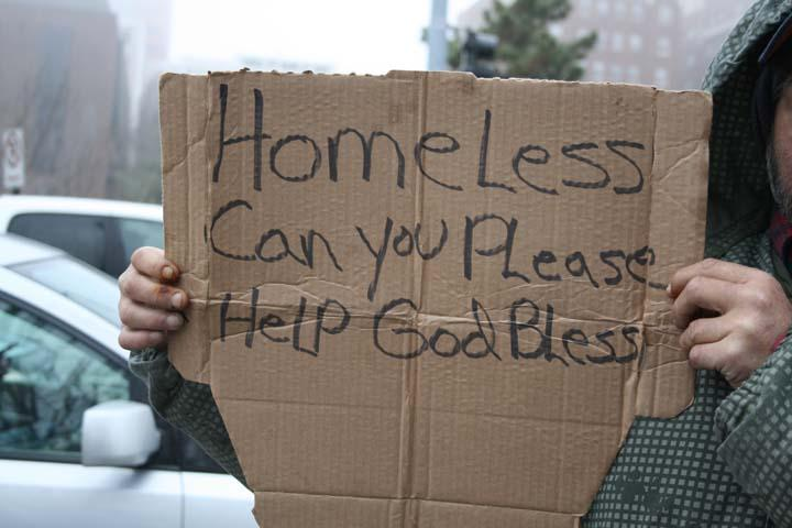 "A person holds up a homemade sign that reads, ""Homeless Can You Please Help God Bless."""